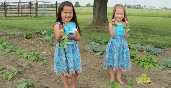 Two of the girls show off their first vegetables of the Spring.