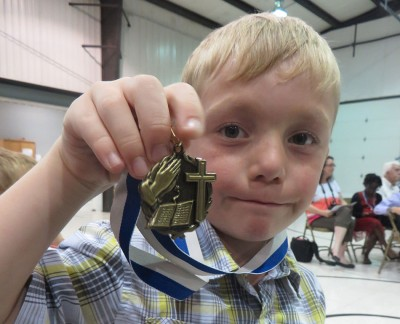 Showing off his memory verse medal