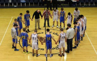 Boy's basketball team prays before game