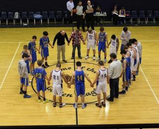 Boy's basketball team prays before game