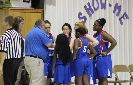 coach going over plays with girls basketball team